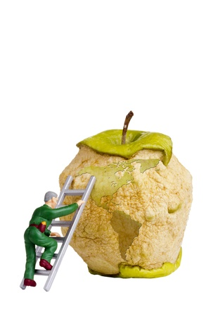 reconstructing: Figurine of a man climbing a ladder on an apple with a silhouette of an earth to fix it. Stock Photo