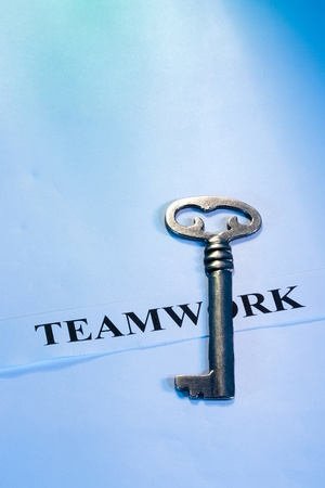 project: A key laying on a piece of paper with the word teamwork on it. Stock Photo
