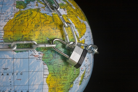 Metal lock and chain on a globe. photo
