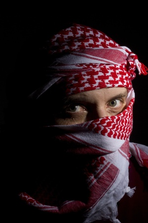 Close-up photograph of a man in a red keffiyeh.