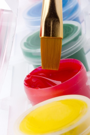 Flat art brush being dipped into a container of red paint. Imagens