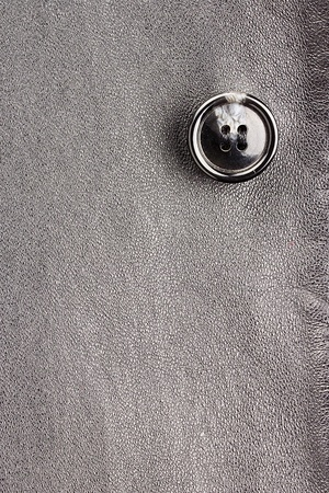 Close-up photograph of a gray button on gray fabric. Add your text to the background.