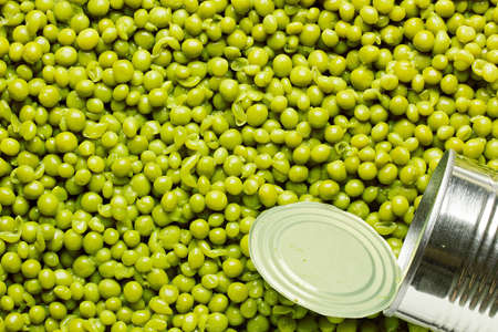 canned peas: Metal can laying on preserved green peas. Add your text to the background.
