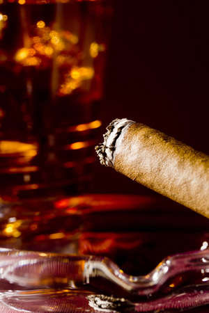 Close-up selective focus of a burning cigar with a glass of whiskey in the background. Stock Photo - 12538838
