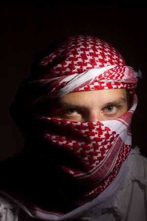 keffiyeh: Close-up photograph of a man in a red keffiyeh.
