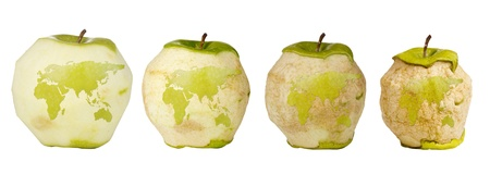 Green apple with a carving of the world map shown four times over a timespan of its deterioration.