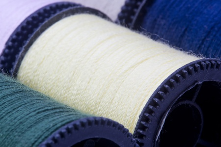Close-up photograph of a yellow spool of thread among other spools. photo