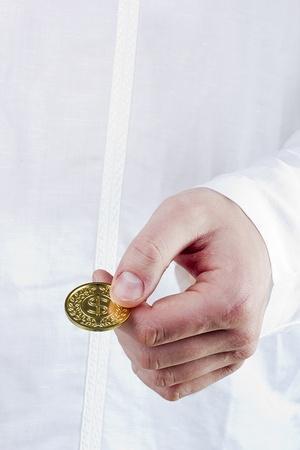 Close-up photograph of a golden coin in a mans hand. photo