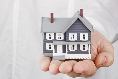 house in hand: Close-up photograph of a miniature house in a mans hand.