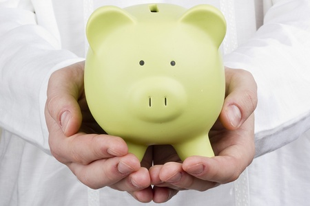 Close-up photograph of a green piggy bank in mans hands. photo