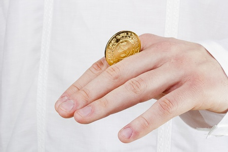 Close-up photograph of a golden coin between a man's fingers. Stock Photo - 13067008