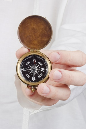 Close-up photograph of a hand holding an old compass. photo
