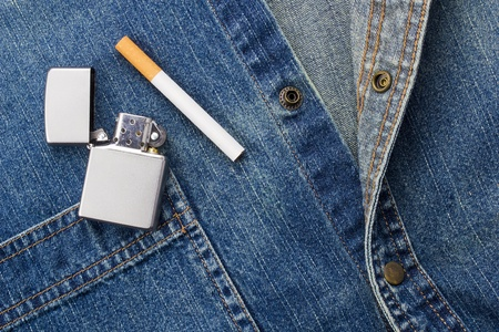 Close-up photograph of a cigarette and a silver lighter laying on denim material. photo