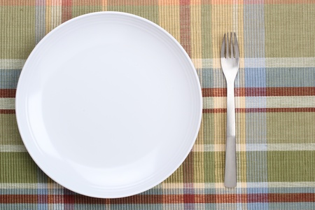 table top: Directly above shot of a white plate and a fork.