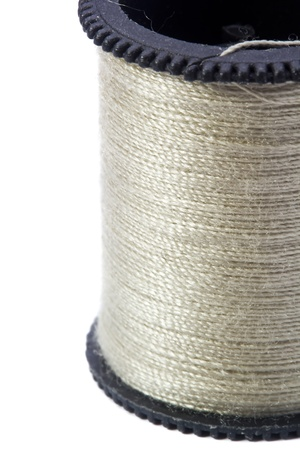 Close-up photograph of gray thread spool on white background. photo