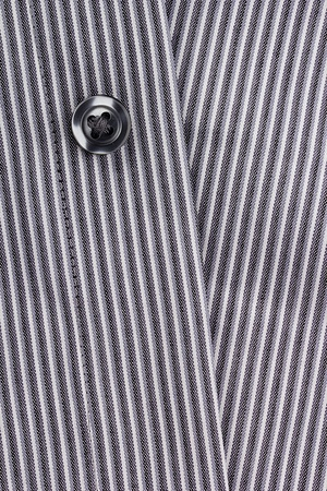 Close-up photograph of a black button on a striped gray pattern. Stock Photo - 13562556