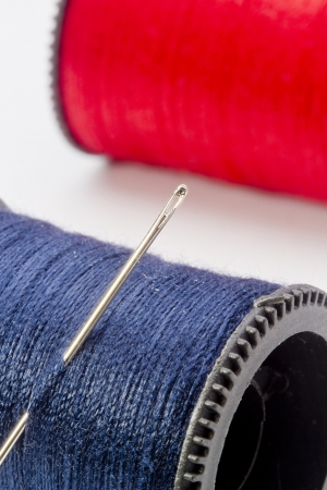 Close-up photograph of a blue thread spool and needle.