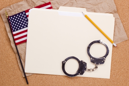 Directly above photograph of handcuffs, folder, and the American flag. photo