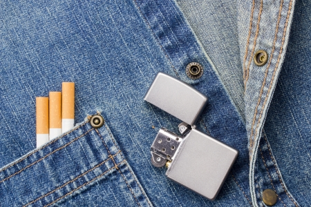 Close-up photograph of cigarettes and a silver light on a denim background. photo