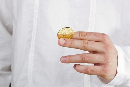 Close-up photograph of a golden coin between a man's fingers. Stock Photo - 14289498