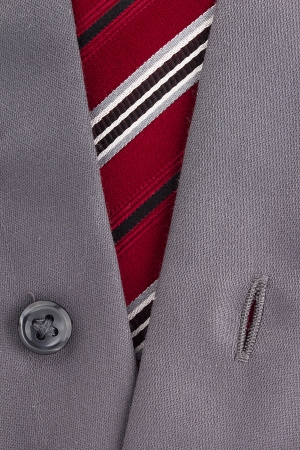 Close-up photograph of a red striped tie with a gray shirt. photo