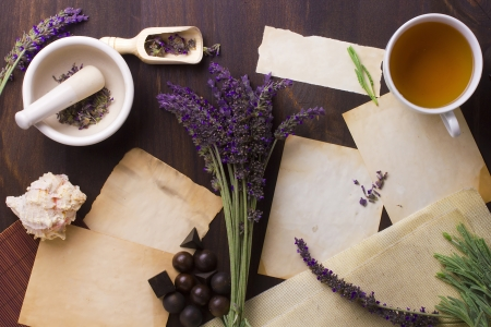 Directly above photograph of lavender flowers, papers, and decorative objects to portray the topic of alternative medicine. Add your text to the papers. photo