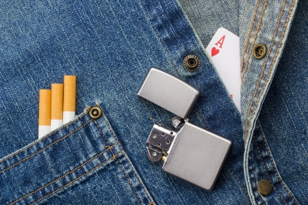 Close-up photograph of cigarettes, silver lighter, and a playing card on a denim background. photo