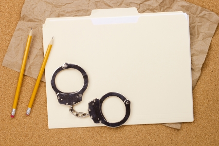 restraints: Directly above photograph of handcuffs and a folder.