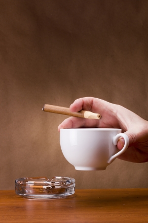 Hand holding a cigarette and a cup ashtray. Stock Photo - 14748528