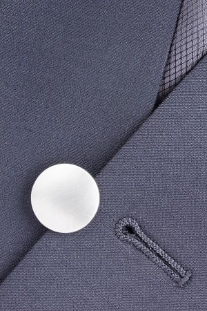 Close-up photograph of a silver button on gray material. photo