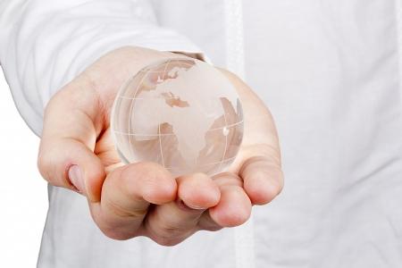 ガラスの球体、人間の手のクローズ アップ写真。