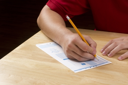 exams: Student filling out answers to a test with a pencil.