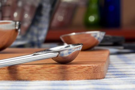 Close-up photograph of a measuring cup on a wooden cutting board. Reklamní fotografie