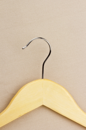 clotheshanger: Close-up of a wooden coat hanger on a gray background.