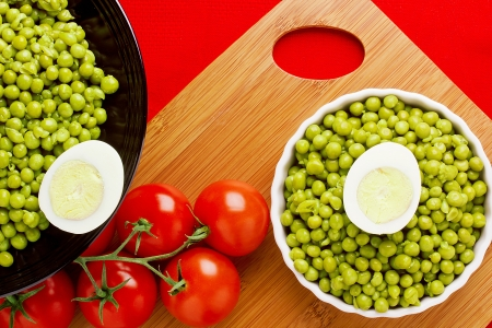 Directly above photograph of eggs, tomatoes, and a plate of peas. photo