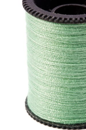 Close-up photograph of green thread spool on a white background. photo