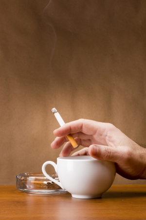 Hand holding a cigarette and a cup ashtray. Stock Photo - 15100068