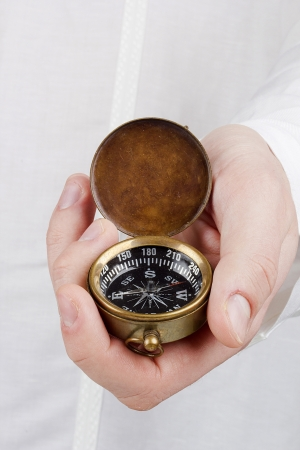 Close-up photograph of a man holding an old compass.