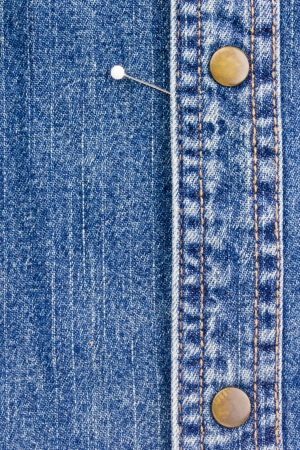 Close-up photograph of a pin on denim material. Add your text to the background. Reklamní fotografie