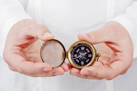 Close-up photograph of a hand holding an old compass. Imagens