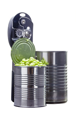 Preserved green peas in a metal can next to a can opener on a white background. Stock Photo - 15397335