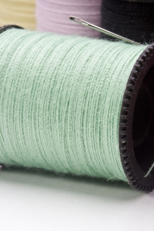 Close-up photograph of a green spool of thread.