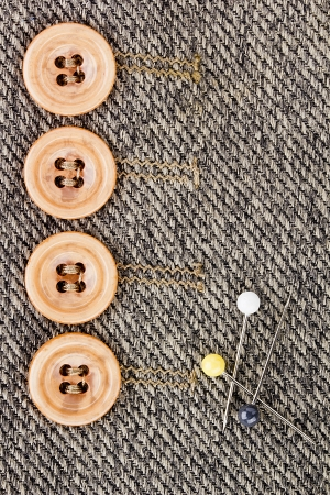 Close-up photograph of four orange buttons next to three pins on gray fabric.