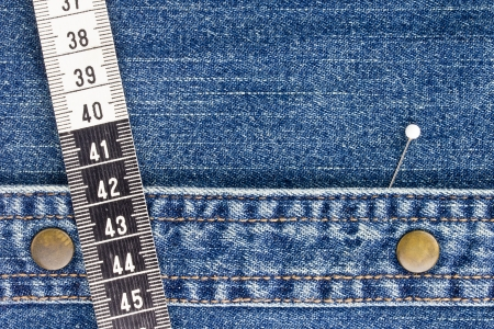 Close-up photograph of measuring tape and a pin on denim material. Add your text to the background. Stock Photo - 15542370
