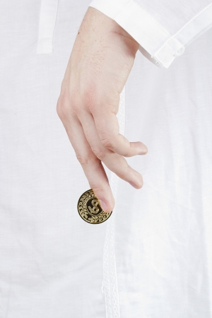 Close-up photograph of a golden coin between a man's fingers. Stock Photo - 15602753