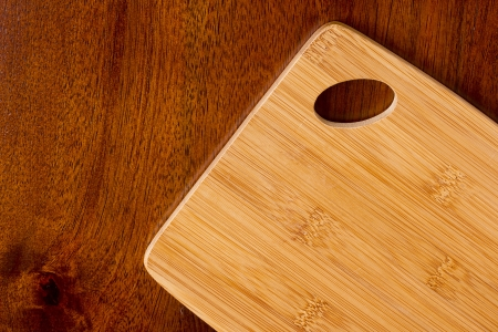 Kitchen board on a wooden surface as background.