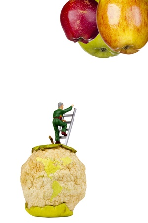 Miniature figure of a man climbing a ladder from a spoiled apple photo