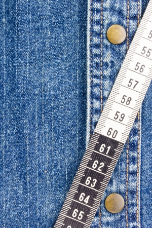 Close-up photograph of measuring tape on denim material. Add your text to the background. Stock Photo - 15914162