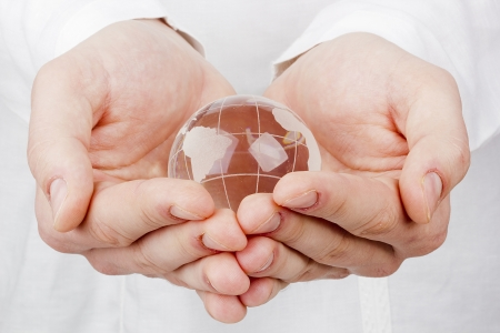 hands holding globe: Close-up photograph of a glass globe in a mans hands.
