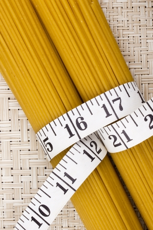Directly above photograph of golden pasta tied with measuring tape. Stock Photo